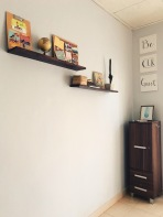 Floating shelves and canvases in guest room